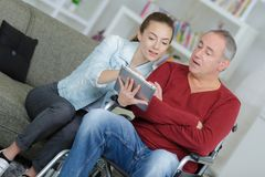 Young woman helping senior man to use tablet. Young women helping a senior men to use a tablet Royalty Free Stock Photos