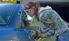 Young Woman Helping to Fix Car Door. This pretty young woman is helping to fix the smashed car door Royalty Free Stock Image