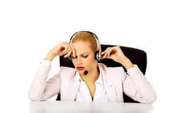 Young woman helpline operator is trying to hear something through a headphones Stock Photo