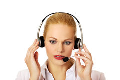 Young woman helpline operator is trying to hear something through headphones Royalty Free Stock Images