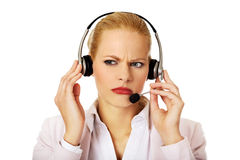 Young woman helpline operator is trying to hear something through headphones.  Royalty Free Stock Images