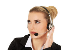 Young woman helpline operator is trying to hear something headphones Royalty Free Stock Photography