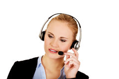 Young woman helpline operator is trying to hear something headphones.  Stock Image