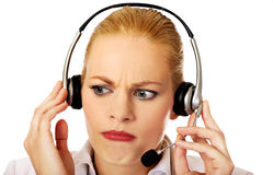 Young woman helpline operator is trying to hear something through headphones Royalty Free Stock Photo