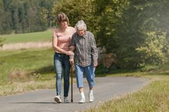 Young woman helps senior woman walking with stick stock photos