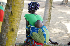 Young woman and her baby. Bassam, Abidjan, Ivory Coast - August 29, 2015: a young woman, her head tied with a scarf, her baby sleeping in her back, sat under a Royalty Free Stock Images