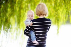Young woman with her baby girl. Happy young women with her baby girl at the spring or summer park Stock Photos