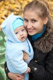 Young woman and her baby son in autumn park Stock Photos