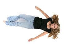 Young woman on her back on the floor with arms out Stock Photo
