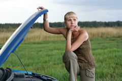 Young woman and her broken car. Young blond woman with her broken car. The girl is sad Royalty Free Stock Photography
