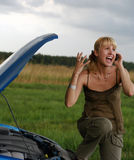 Young woman and her broken car. Young blond woman with her broken car. The girl is angry Royalty Free Stock Photography