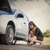 Young woman with her broken car Stock Image