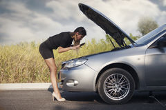Young woman with her broken car Stock Photos