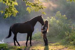 Young woman with her brown horse on a beautiful landscape. Clear lake at morning fog. Sunrise royalty free stock photo