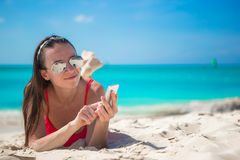 Young woman with her cell phone on exotic beach Stock Photography