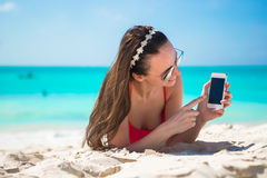 Young woman with her cell phone on white beach stock photos