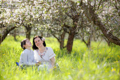 Young woman and her child having rest in spring apple garden Royalty Free Stock Image