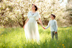 Young woman and her child having rest in spring apple garden Stock Images