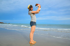 Young woman with her cute jack russel puppy on the beach Stock Images