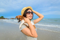 Young woman with her cute jack russel puppy on the beach Stock Photography