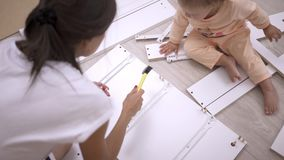 A young woman with her daughter, assemble furniture according to the instructions, hammering nails with a hammer stock video footage