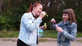 A young woman with her daughter blowing bubbles in the Park on a summer evening, mother`s day . Family relation stock video footage
