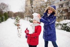 Young woman and her daughter cheerfully spend time on street in winter day. Royalty Free Stock Photos