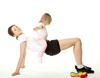 Young woman and her daughter doing sport exercises Stock Images