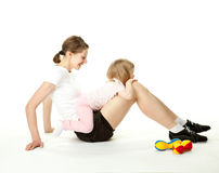 Young woman and her daughter doing sport exercises Stock Photos