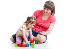 Young woman and her daughter kid play with building blocks Royalty Free Stock Image