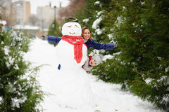 The young woman and her daughter look out because of a big snowman. Stock Photos
