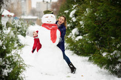 The young woman and her daughter look out because of a big snowman Stock Images