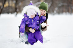 Young woman with her daughter playing with snow at the park Royalty Free Stock Image