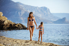 Young woman and her daughter walking along beach Royalty Free Stock Photography