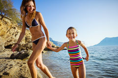 Young woman and her daughter walking along sandy beach Royalty Free Stock Image