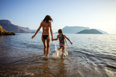 Young woman and her daughter walking in shallow sea waters. Young women and her daughter walking in shallow sea waters, girl splashing around stock photos