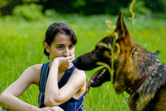 Young woman with her dog. Woman sitting on green grass field and watching her German Shepherd dog Stock Photography