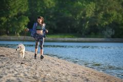 Young woman with her dog on beach. Pet care. Young woman with her dog together on beach. Pet care Stock Photo