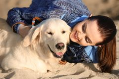 Young woman with her dog on beach. Pet care. Young woman with her dog together on beach. Pet care Stock Image