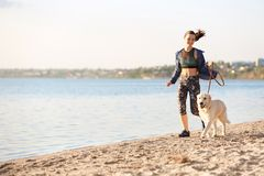 Young woman with her dog on beach. Pet care. Young woman with her dog together on beach. Pet care Royalty Free Stock Image