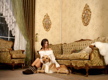 A young woman with her dog in a luxurious room Stock Images