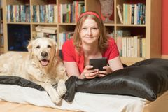 Young woman and her dog are lying indoors royalty free stock images