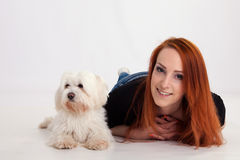 Young woman with her dog. Young redhead woman with her white Maltese dog in studio Royalty Free Stock Photography