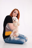 Young woman with her dog. Young redhead woman with her white Maltese dog in studio Stock Images