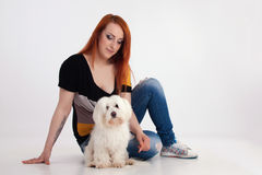 Young woman with her dog. Young redhead woman with her white Maltese dog in studio Stock Photos