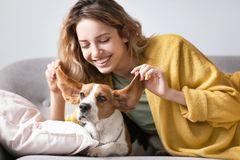 Young woman with her dog resting on sofa. At home Royalty Free Stock Images