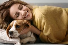 Young woman with her dog resting on sofa. At home Stock Photo