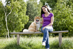 A young woman and her dog sitting on a bench Stock Images