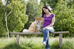 A young woman and her dog sitting on a bench Royalty Free Stock Images