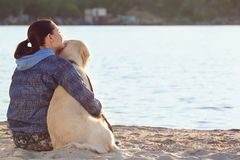 Young woman with her dog together on beach stock photo